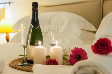 Wine, candles, and flowers on a bed