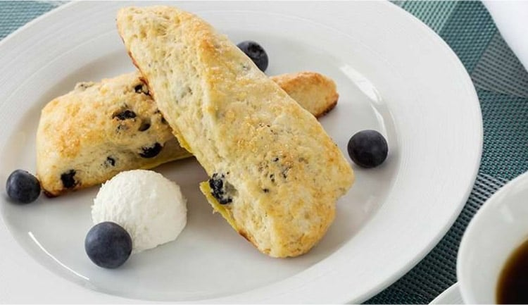 Scones plated with a scoop of butter and a handful of blueberries sprinkled around
