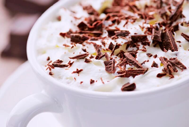 Closeup of a cup of hot chocolate with froth and shredded chocolate on top