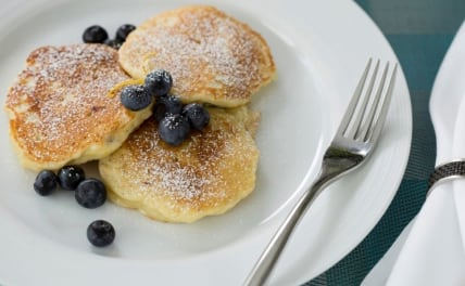 Breakfast of three small pancakes with blueberries sprinkled around them