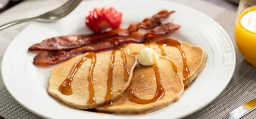 Plated pancake with syrup and bacon