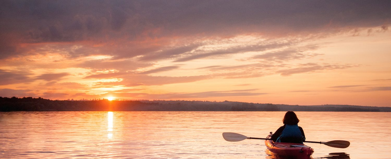 Woman kayaking solo on river at sunset.